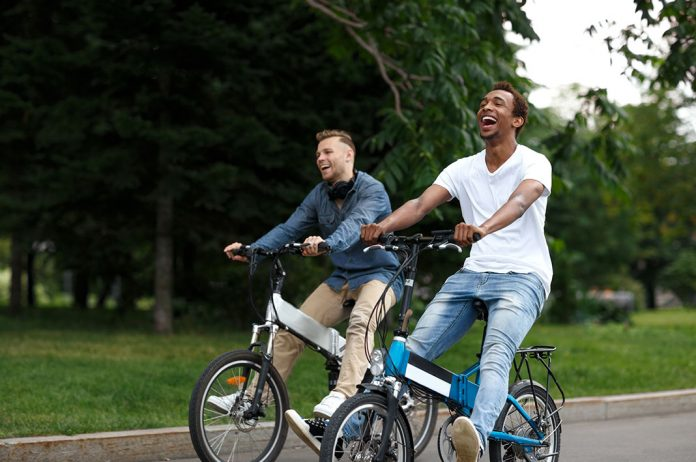 Two men riding on a cycle powered by a motor and a battery I iTMunch