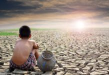 A boy sitting with pot on a barren land due to climate change and looking towards sun I iTMunch