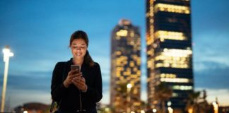 A girl using mobile phone in the city | iTMunch