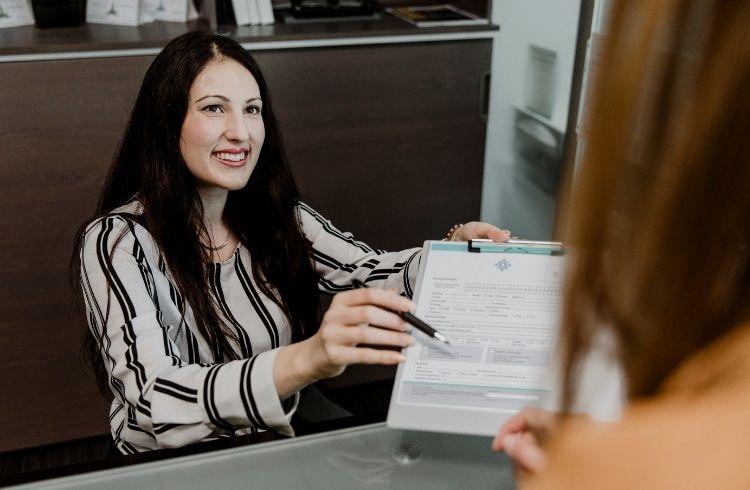 Women handing a contract to an employee